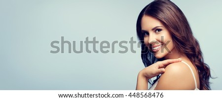 Portrait of beautiful cheerful smiling young woman, with blank copyspace area for text or slogan - stock photo