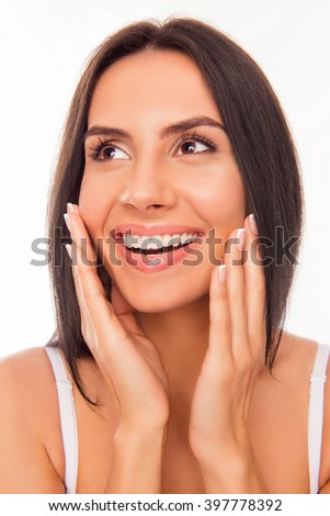 Portrait of beautiful cheerful woman touching her face and smiling - stock photo