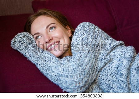 Portrait of beautiful cheerful young woman in grey knitted sweater lying on couch - stock photo