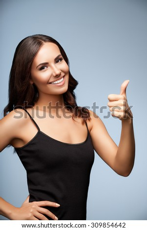 Portrait of beautiful cheerful young woman showing thumb up hand sign gesture, over grey background - stock photo