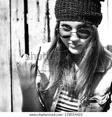 portrait of beautiful cool girl gesturing in hat and sunglasses, black and white - stock photo