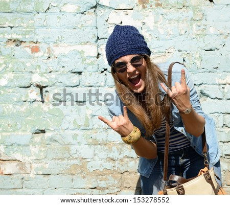 portrait of beautiful cool girl gesturing in hat and sunglasses over grunge wall - stock photo