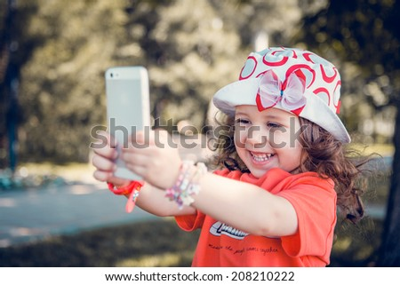 Portrait of beautiful curly amazing little girl laughs and takes pictures of themselves outdoors on a sunny day, a little girl taking a selfie - stock photo