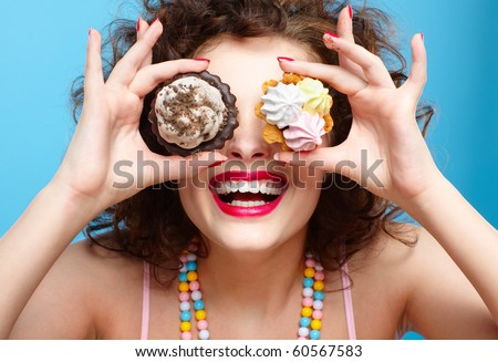 portrait of beautiful curly brunette girl with two tarts
