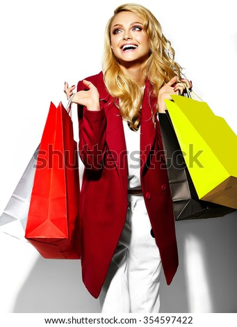 portrait of beautiful cute happy sweet surprised blonde woman girl holding in her hands big shopping colorful bags in hipster red clothes isolated on white - stock photo