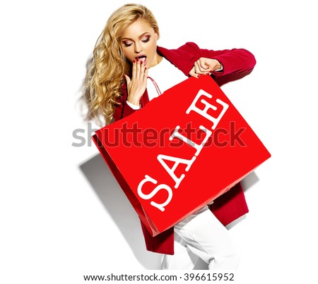 portrait of beautiful cute happy sweet surprised blonde woman girl holding in her hands big shopping bag in hipster red clothes isolated on white - stock photo