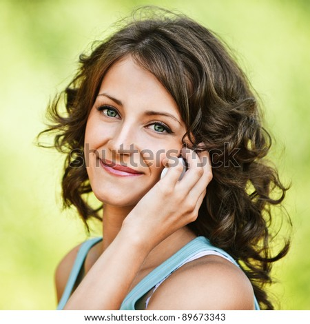 Portrait of beautiful dark-haired curly young woman wearing blue t-shirt, speaking on mobile phone at summer green park. - stock photo