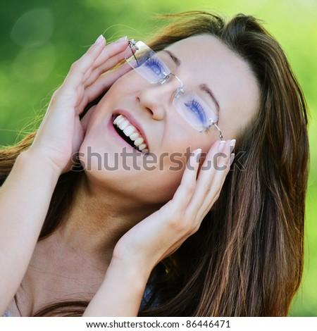 Portrait of beautiful dark-haired girl wearing eyeglasses at summer green park. - stock photo