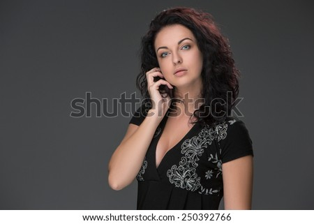 Portrait of beautiful dark-haired young woman, speaking on mobile phone against a dark background - stock photo