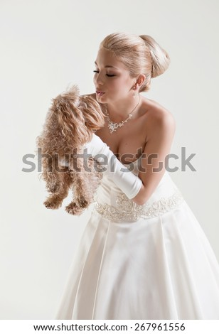 Portrait of beautiful delicate blonde bride in a wedding dress kissing small beige dog , on a white background in the Studio - stock photo