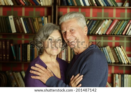 Portrait of beautiful elderly couple over book shelves