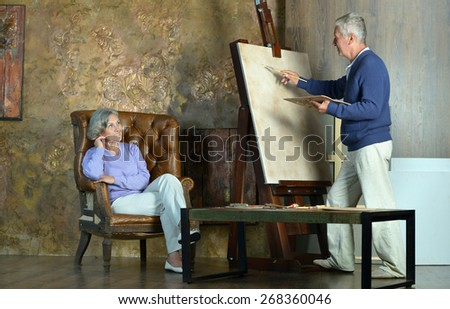 Portrait of beautiful elderly couple painting with easel - stock photo