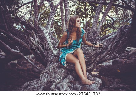 Portrait of beautiful elegant lady  with dress in a green jungle rainforest. Retro colors - stock photo