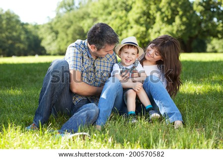 Portrait of beautiful family having fun in a meadow - stock photo