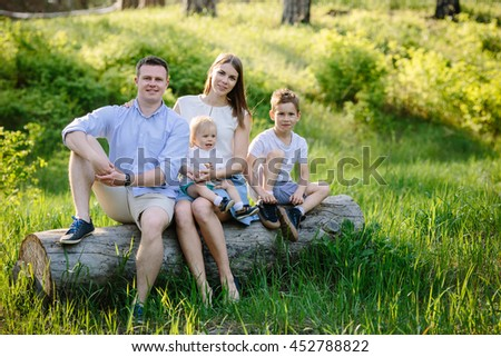 Portrait of beautiful family of four people mother father son daughter sitting on a log picnic in the park near forest - stock photo