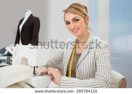 Portrait Of Beautiful Fashion Designer Working On Sewing Machine In Studio - stock photo