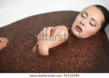 Portrait of beautiful fashion girl in jacuzzi with coffee. Body care. bright makeup - stock photo