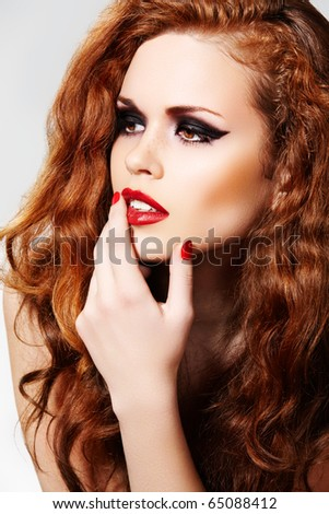 Portrait of beautiful fashion woman model with luxury evening make-up, dark eyeshadows, bloody lips and chic long curly red hair.  Vamp female style.