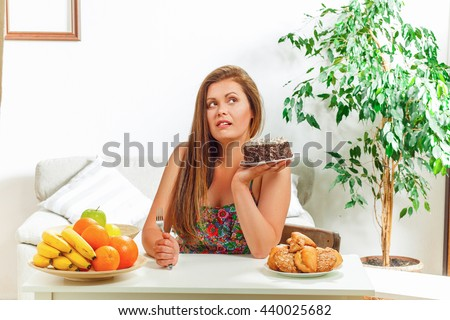 Portrait of beautiful fat woman on diet sitting at table at home and looking away. Pretty lady thinking whether to eat it or not. - stock photo