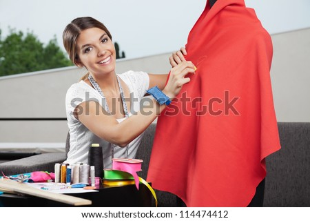 Portrait of beautiful female fashion designer working on  red fabric with dressmaking accessories on table - stock photo