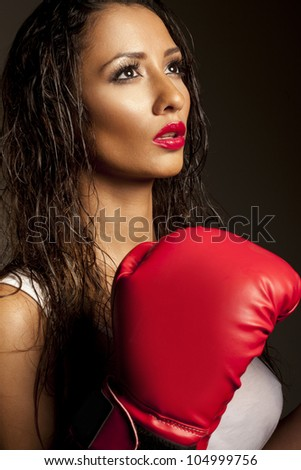 Portrait of beautiful female fighter with red boxing gloves on black background - stock photo