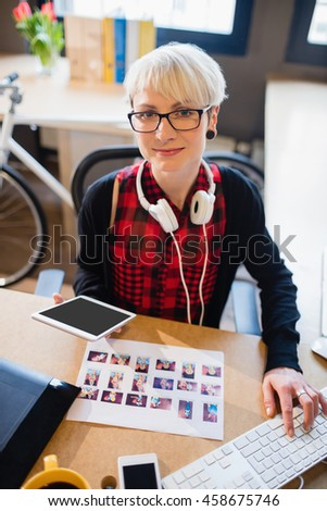 Portrait of beautiful female graphic designer working on computer at office