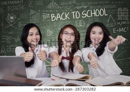 Portrait of beautiful female high school students back to school and showing thumbs up in the class - stock photo
