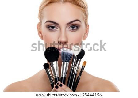 Portrait of beautiful female model holding make-up brushes - stock photo