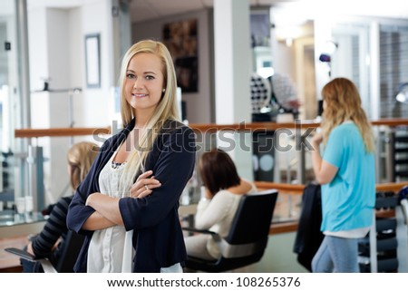Portrait of beautiful female owner of parlor standing arms crossed with customers in background - stock photo