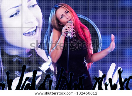 Portrait of beautiful female singer with a microphone on stage - stock photo