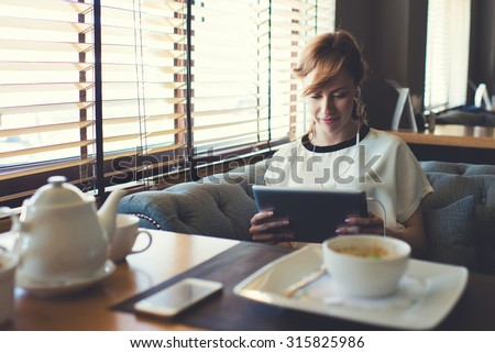 Portrait of beautiful female student listen or studying on-line training course in headphones while using her digital tablet charming young woman have video conversation while breakfast in coffee shop - stock photo