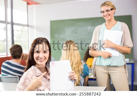 Portrait of beautiful female student pointing at paper in the class - stock photo