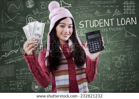 Portrait of beautiful female student wearing winter clothes and holding money with calculator in class - stock photo