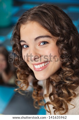 Portrait of beautiful female teacher smiling in classroom - stock photo