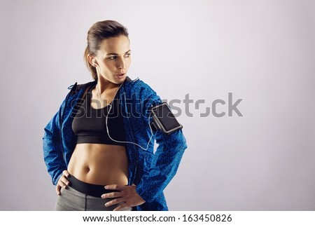 Portrait of beautiful fitness woman wearing sportswear looking away at copyspace while standing on grey background. Young caucasian female in sports gear posing. - stock photo
