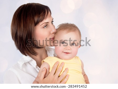 Portrait of beautiful gentle mother kissing her precious little baby over blur background, young loving family, enjoying motherhood