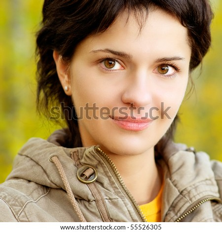 Portrait of beautiful girl against trees with yellow foliage. - stock photo