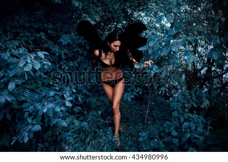 Portrait of beautiful girl angel with black wings on the nature forest grass greens