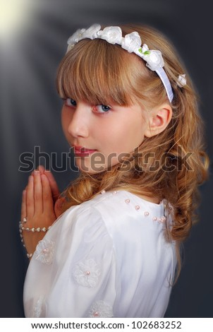 portrait of beautiful girl going to the first holy communion and posing in studio against dark background with lights - stock photo