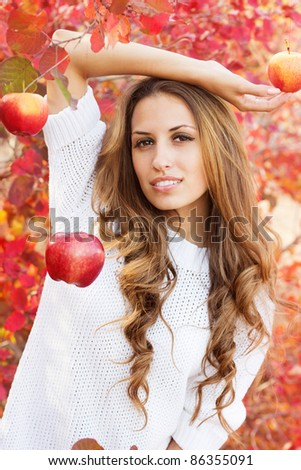 portrait of beautiful girl in autumn leaves. Apple in hand.