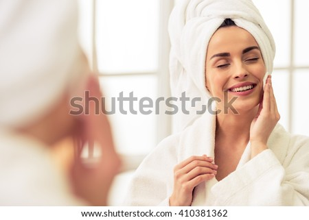 Portrait of beautiful girl in bathrobe and with towel on her head cleaning her face with sponge and smiling, standing with closed eyes - stock photo