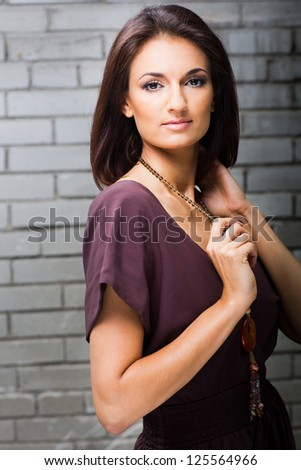 Portrait of beautiful girl in brown dress posing against brick wall - stock photo