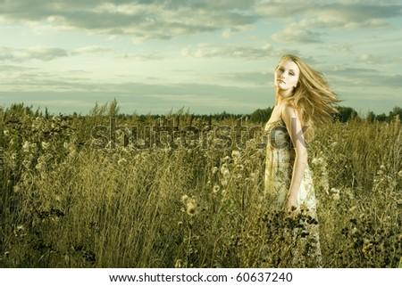 Portrait of beautiful girl in field - stock photo