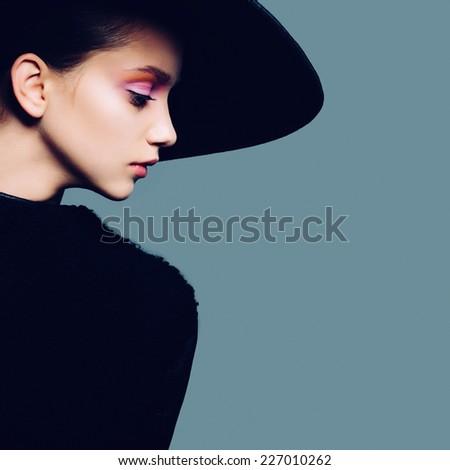 Portrait of beautiful girl in hat in profile, posing in studio - stock photo
