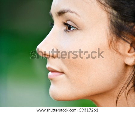 Portrait of beautiful girl in profile, on green background. - stock photo