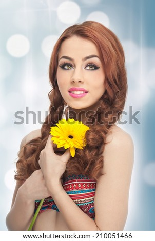 Portrait of beautiful girl in studio with yellow chrysanthemum in her hands. Sexy young woman with blue eyes with bright flowers. Redhead, creative hairstyle and makeup, fashion photo studio shot - stock photo