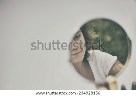 Portrait of beautiful girl, she is looking at the mirror  - stock photo