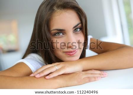 Portrait of beautiful girl sitting in sofa - stock photo