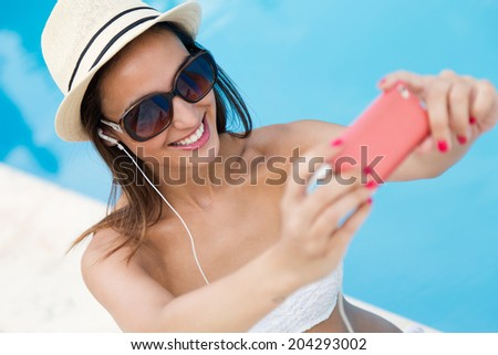 Portrait of beautiful girl taking a selfie at the swimming pool. - stock photo