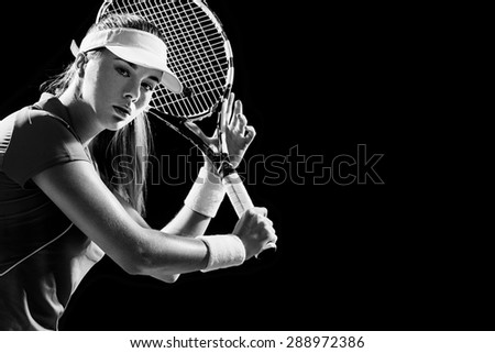Portrait of beautiful girl tennis player with a racket isolated on black background - stock photo